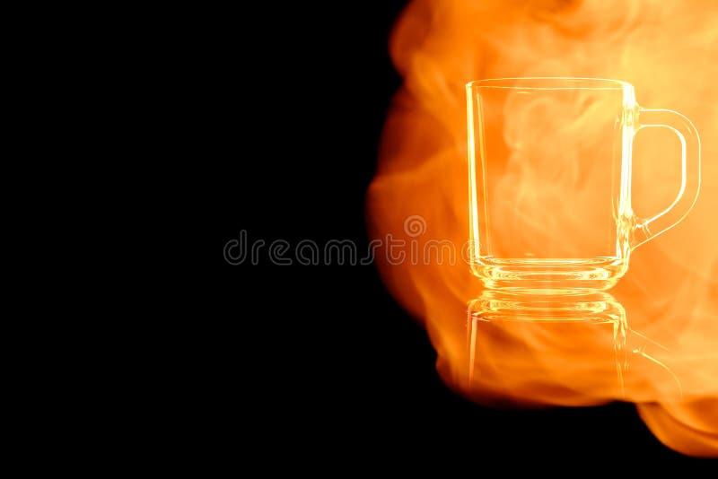 La tasse en verre vide d'en pour le thé dans le feu flambe photos stock