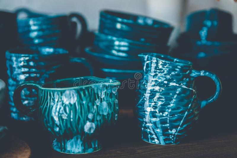 La tasse et la cruche de vaisselle de métier fabriquées à la main de l'argile, ont passé étuver le glaçage photographie stock libre de droits