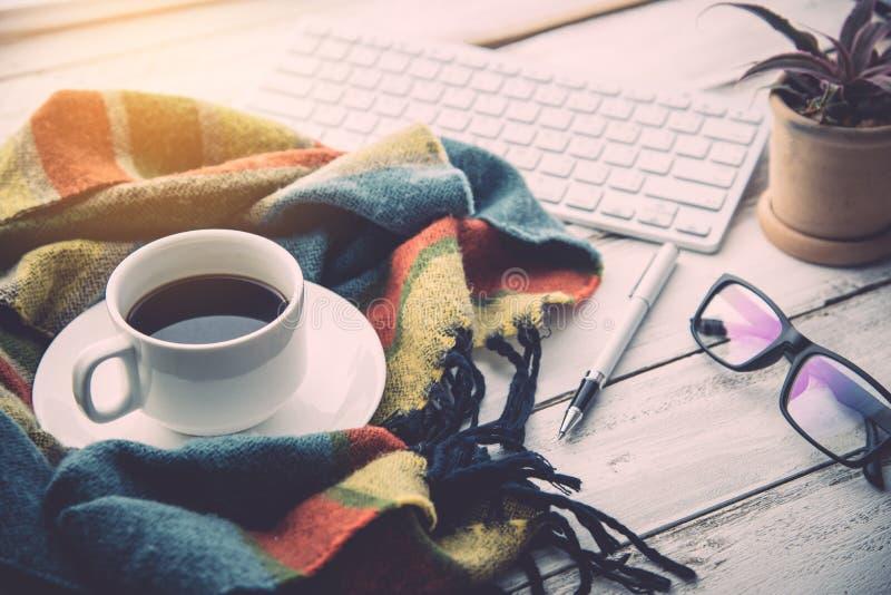 La tasse et l'écharpe de café est placée sur un plancher en bois photo libre de droits