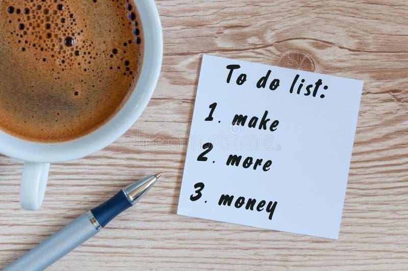 La tasse et le carnet de café avec pour faire la liste gagnent plus d'argent sur le bureau rustique à partir d'en haut, investiss photographie stock libre de droits
