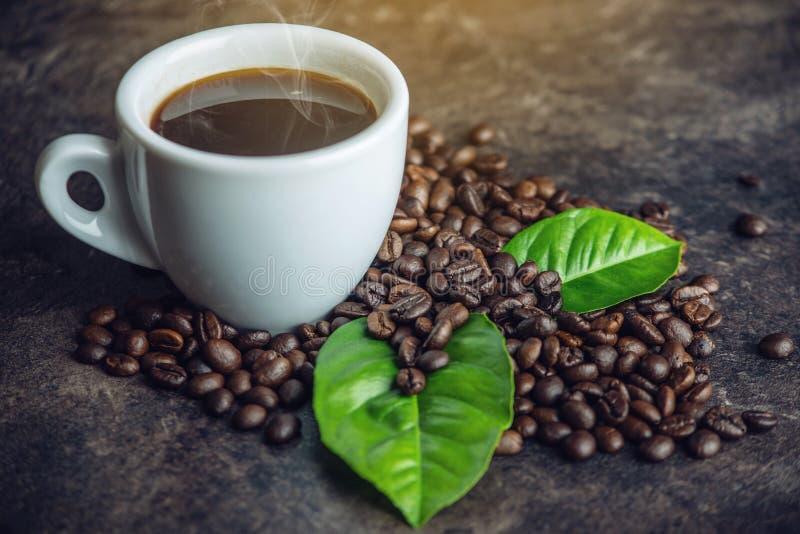 La tasse noire blanche d'expresso avec la pile des grains de café et du vert part dans le sac sur le fond foncé photos libres de droits