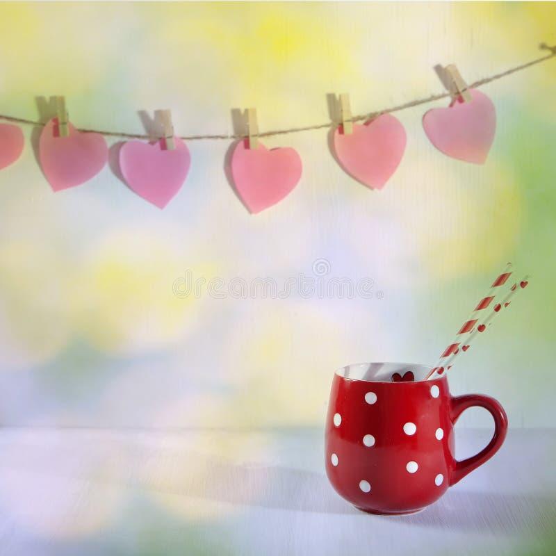 La tasse rouge à un point blanc est sur une table en bois blanche Coup de papier de coeurs sur le mur image stock
