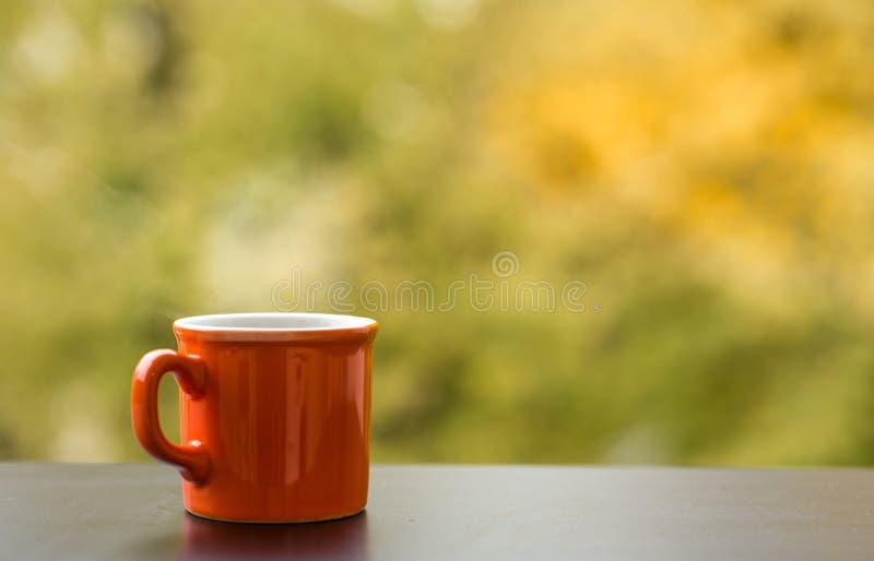 La tasse rouge de la boisson chaude sur un café ajournent dehors image libre de droits