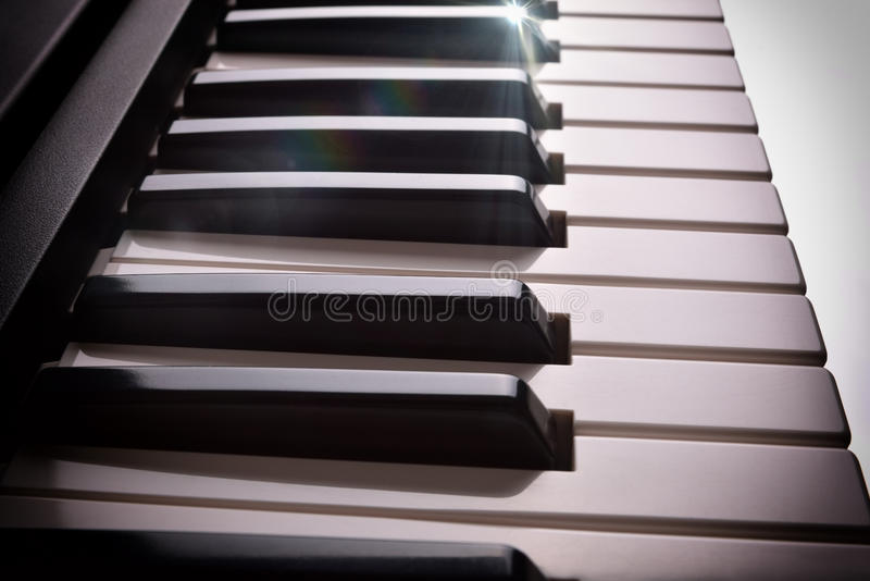 La tastiera di piano elettronica in ombra con lustro ha elevato la vista laterale fotografia stock