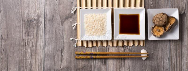 La tavola asiatica degli ingredienti con i bastoncini, il riso, la salsa di soia e lo shitake si espande rapidamente fotografie stock libere da diritti