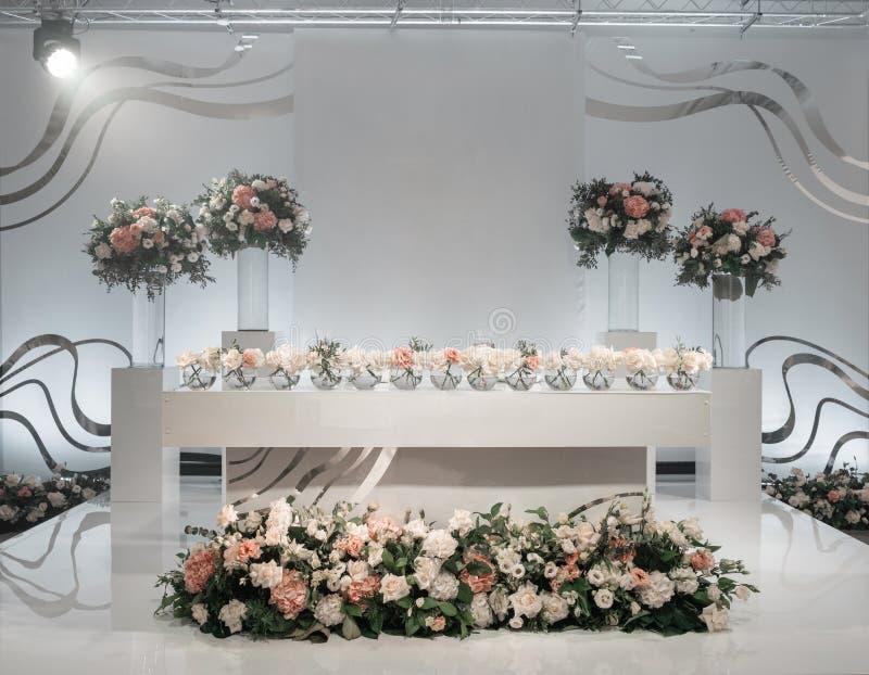 La tavola delle persone appena sposate Piccole disposizioni dei fiori in vasi di vetro della palla Interno del ristorante per la  fotografia stock libera da diritti