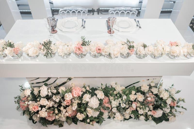 La tavola delle persone appena sposate Piccole disposizioni dei fiori in vasi di vetro della palla Interno del ristorante per la  fotografie stock libere da diritti