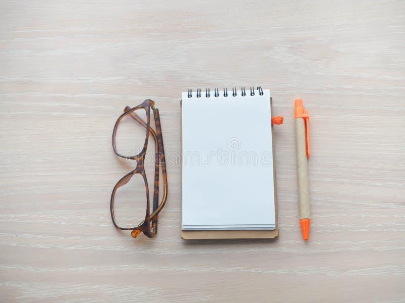 La tavola di legno con lo schermo in bianco per testo sulla carta del blocco note, disegna a matita la a immagini stock libere da diritti