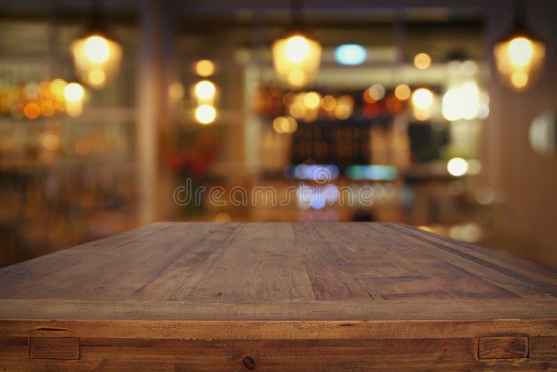 la tavola di legno davanti al ristorante astratto accende il fondo immagine stock libera da diritti