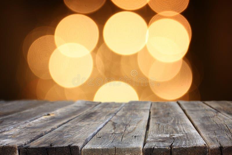 La tavola di legno rustica davanti al bokeh luminoso dell'oro di scintillio si accende fotografia stock