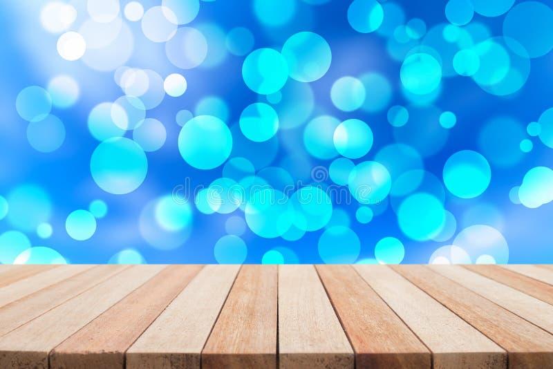 La tavola di legno superiore vuota e l'estratto soleggiato hanno offuscato il backgrou del bokeh fotografie stock