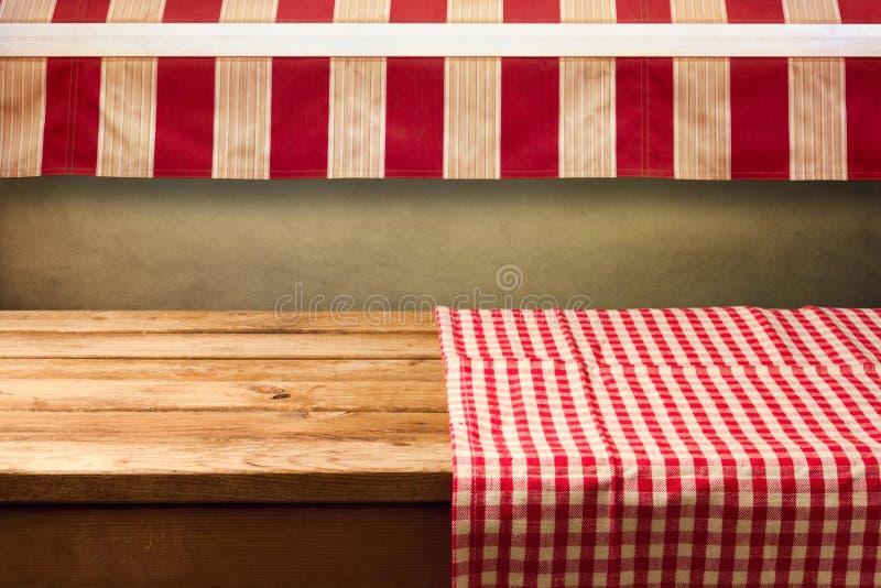 La tavola di legno vuota coperta di rosso ha controllato la tovaglia Fondo per il montaggio del prodotto fotografia stock
