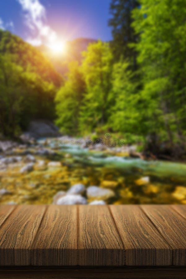 La tavola di legno vuota davanti a fondo vago astratto in natura, può essere usata per esposizione o il montaggio i vostri prodot fotografie stock
