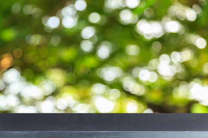 La tavola di pietra superiore vuota e l'estratto soleggiato hanno offuscato il bokeh fotografia stock