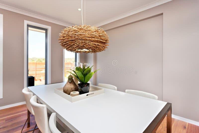 La tavola dinning lussuosa della stanza ha installato con le sedie e il deco naturale fotografia stock