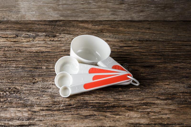 La tavola stabilita di misurazione dà il colore a cucchiaiate bianco su fondo di legno fotografie stock