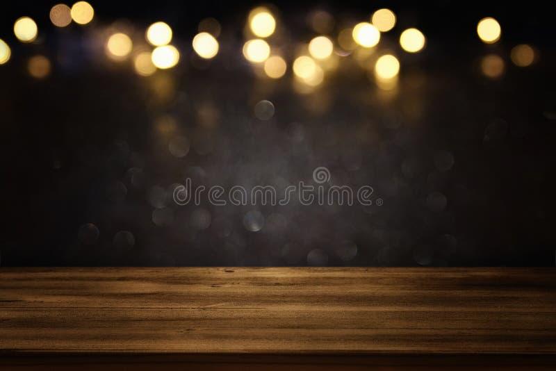 La tavola vuota davanti al nero ed allo scintillio dell'oro accende il fondo fotografie stock libere da diritti