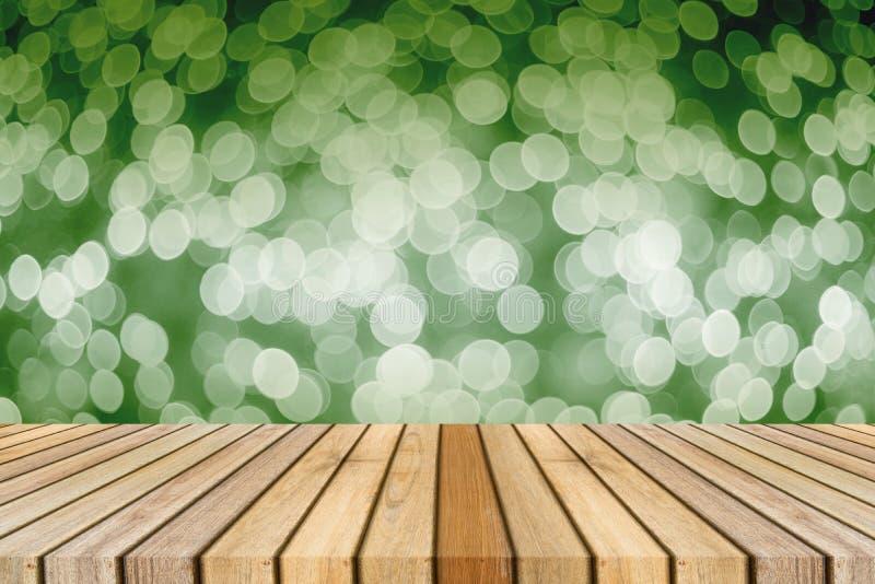 La tavola vuota del bordo di legno davanti a luce sfuocato ha offuscato il fondo per presentare i vostri prodotti Derisione sui v fotografie stock