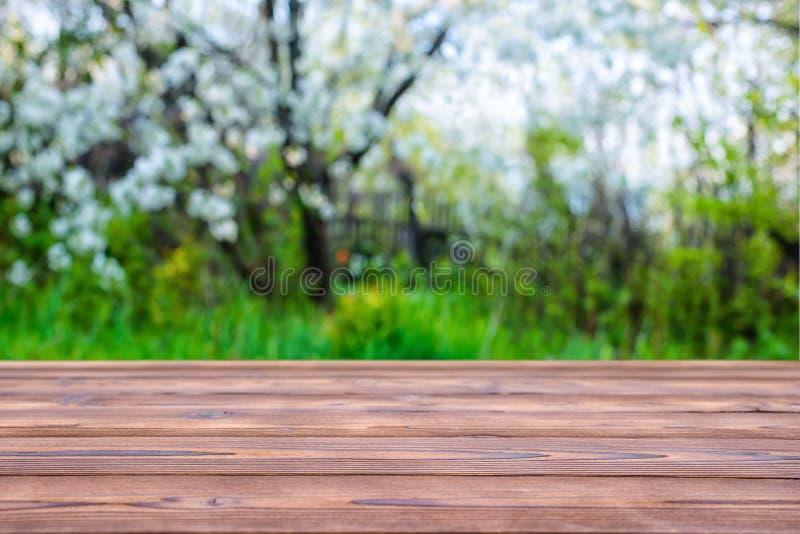 La tavola vuota di legno sopra l'estratto ha offuscato il fondo di bello fotografie stock libere da diritti