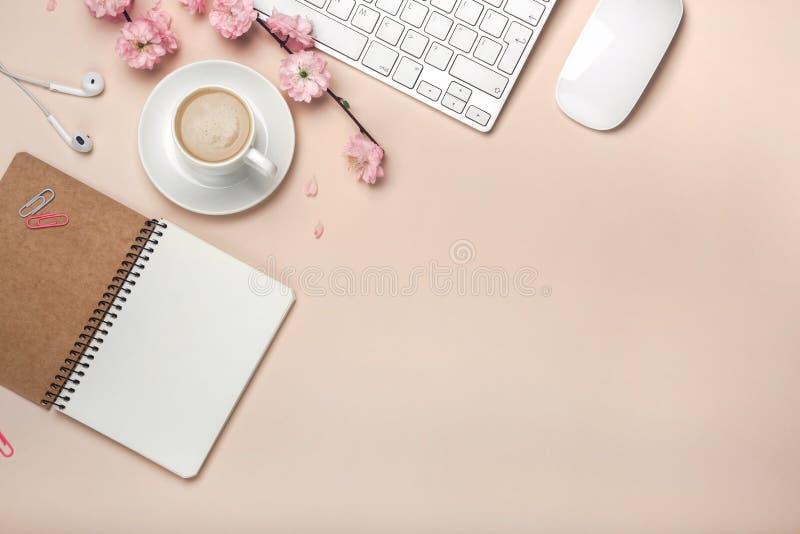 La taza blanca con el capuchino, Sakura florece, teclado, despertador, cuaderno en un fondo del rosa en colores pastel imagen de archivo libre de regalías