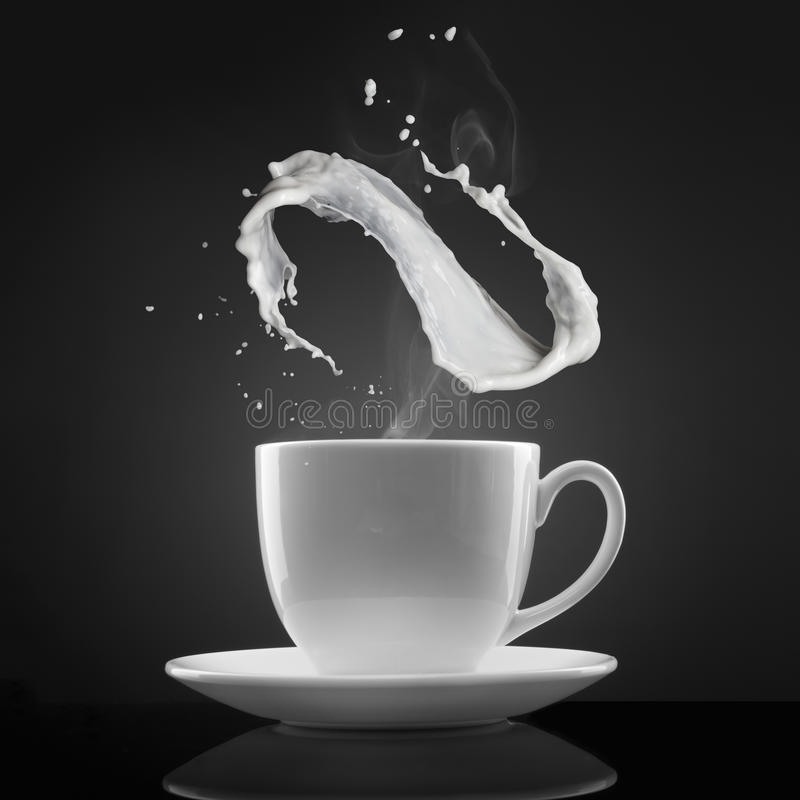 La taza blanca con el líquido caliente y la leche salpican en negro imágenes de archivo libres de regalías