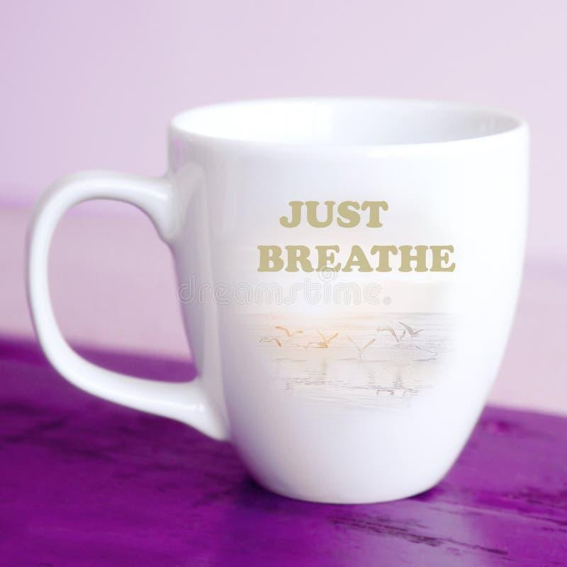 La taza blanca con las palabras apenas respira foto de archivo libre de regalías