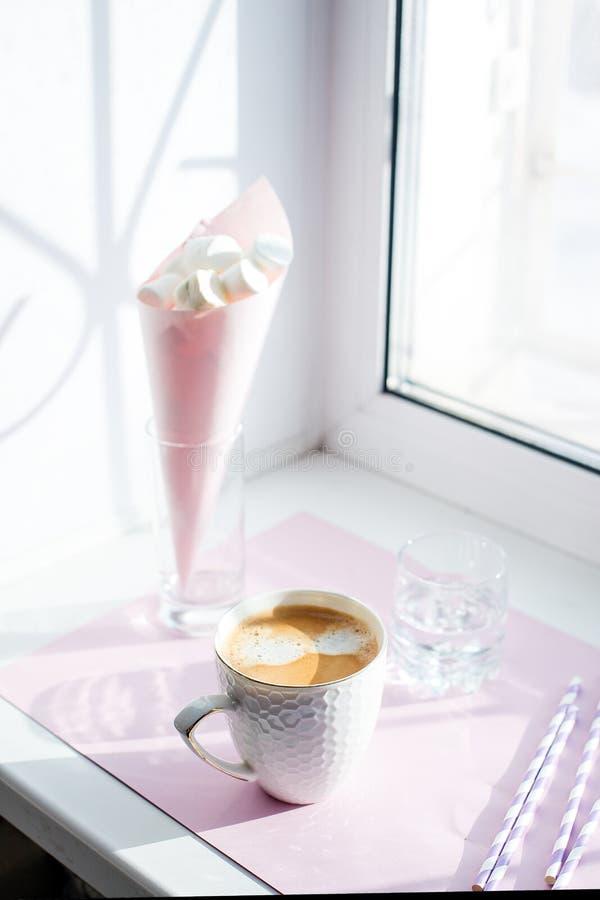 La taza blanca de café caliente contra ventana con la luz de la mañana Concepto mínimo rutinario de la mañana imagen de archivo libre de regalías
