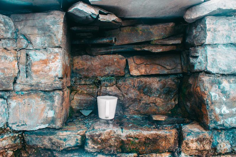 La taza blanca se llena de agua a partir de una primavera natural imágenes de archivo libres de regalías