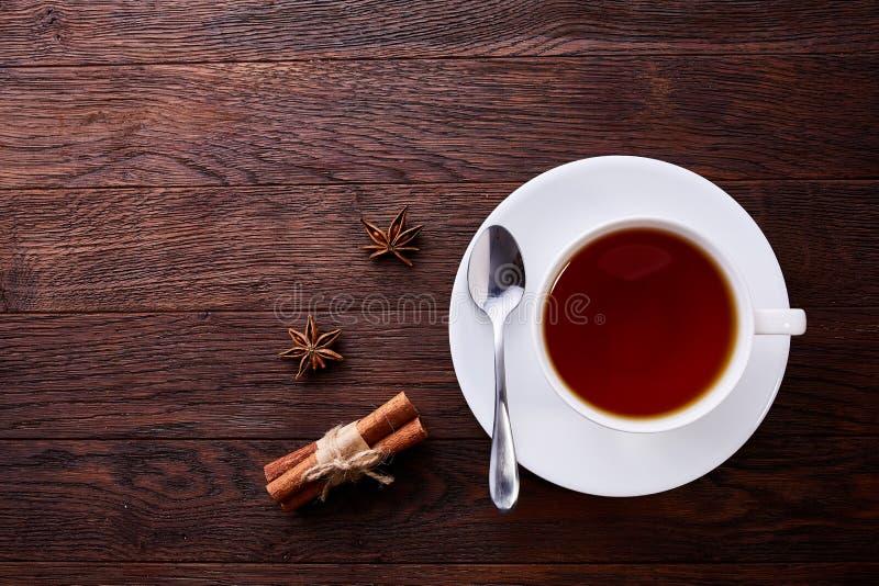 La taza china blanca de la porcelana de té negro y el platillo con anís del canela y de estrella en vintage presentan el fondo Vi imagenes de archivo