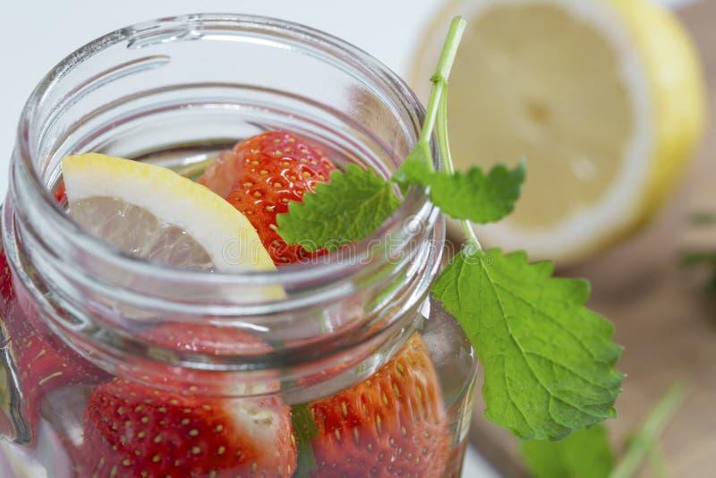La taza de agua de la fruta con las fresas, menta y limón, se coloca en un soporte de madera al lado de las fresas frescas, hojas imagen de archivo libre de regalías