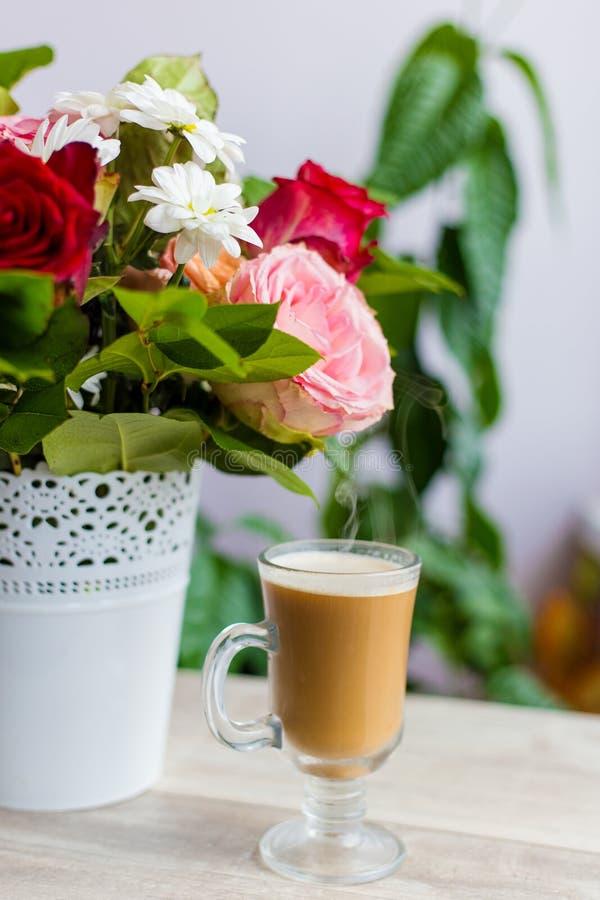La taza de café caliente con leche se coloca cerca de la ventana y de un ramo coloreado brillante de flores fotografía de archivo libre de regalías