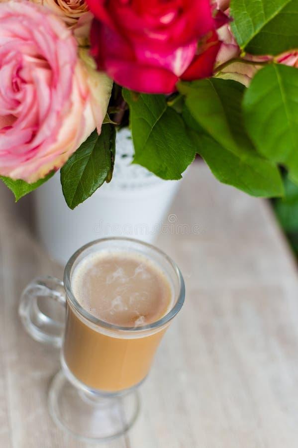 La taza de café caliente con leche se coloca cerca de la ventana y de un ramo coloreado brillante de flores imagenes de archivo