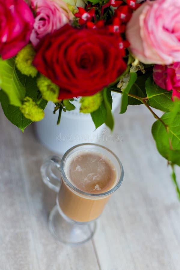 La taza de café caliente con leche se coloca cerca de la ventana y de un ramo coloreado brillante de flores foto de archivo libre de regalías