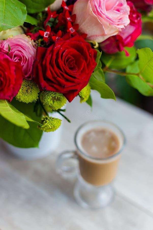 La taza de café caliente con leche se coloca cerca de la ventana y de un ramo coloreado brillante de flores imagen de archivo