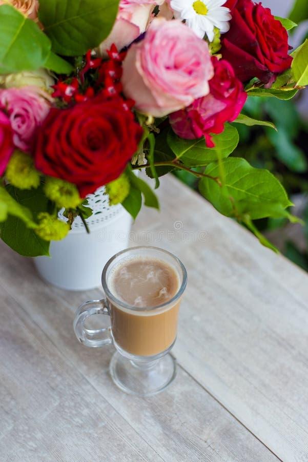 La taza de café caliente con leche se coloca cerca de la ventana y de un ramo coloreado brillante de flores fotografía de archivo