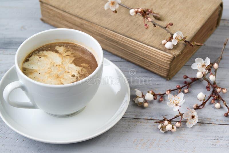 La taza de café con crema y del libro viejo con la cereza floreciente ramifica en fondo de madera fotografía de archivo