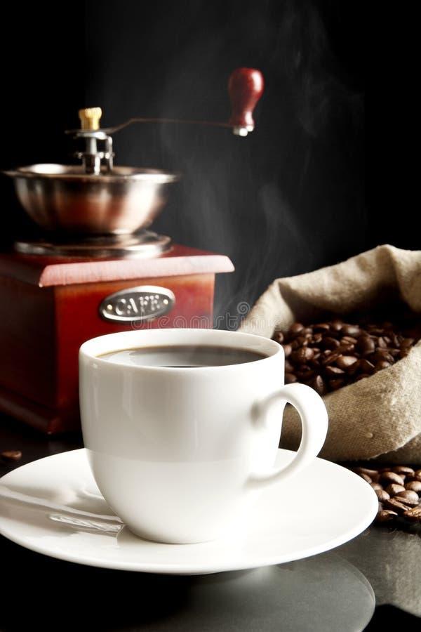 La taza de café con el molino, empaqueta por completo de los granos de café en negro foto de archivo libre de regalías