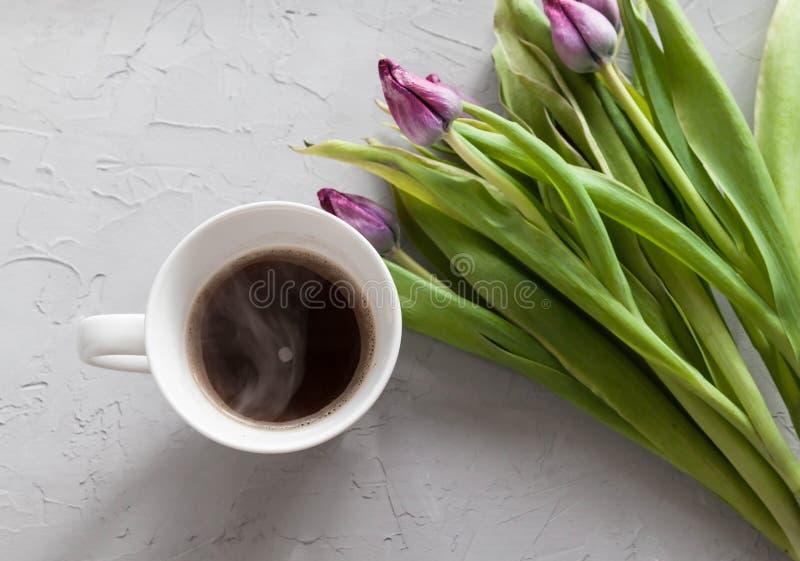 La taza de café con el tulipán púrpura florece en un fondo concreto gris desde arriba, desayuno foto de archivo libre de regalías