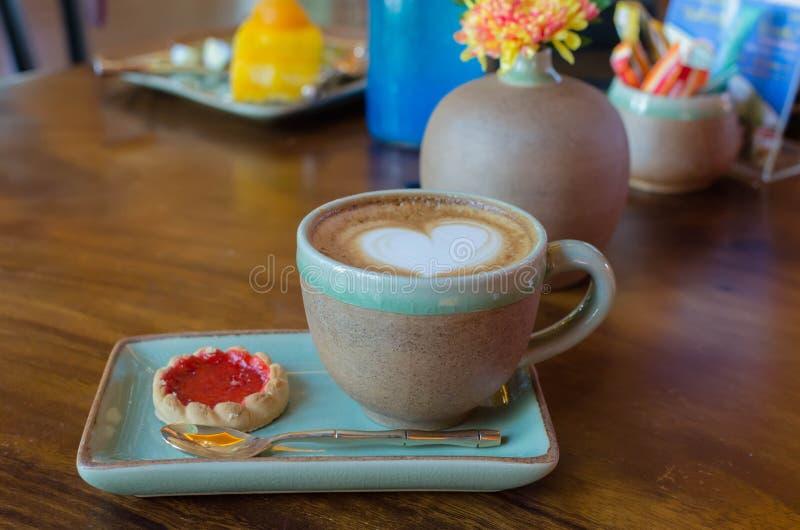 la taza de café con forma del corazón con la galleta de la fresa en azul plat imagen de archivo libre de regalías