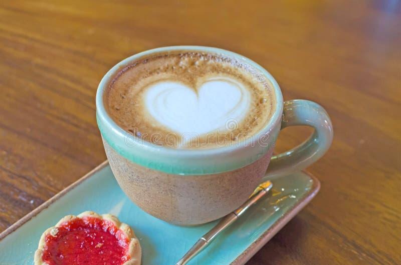 la taza de café con forma del corazón con la galleta de la fresa en azul plat fotos de archivo