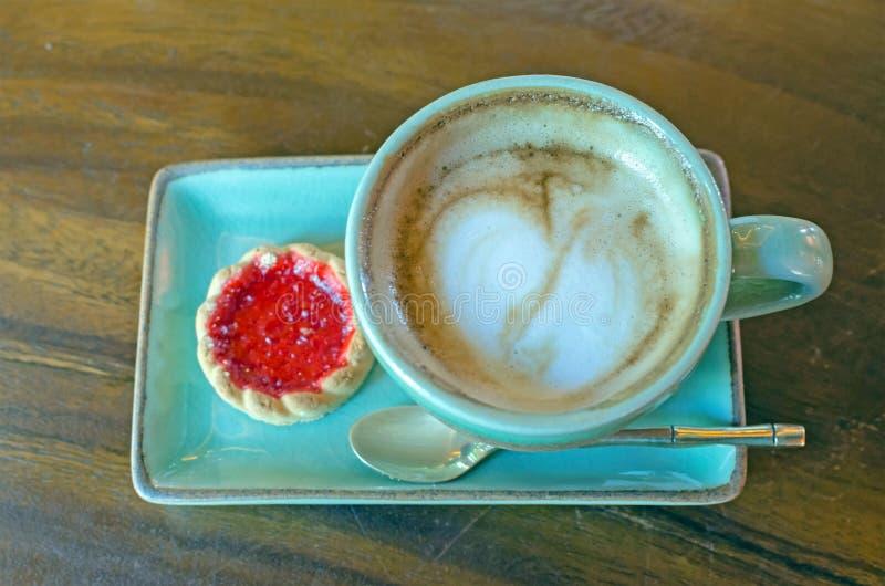 la taza de café con forma del corazón con la galleta de la fresa en azul plat imagen de archivo