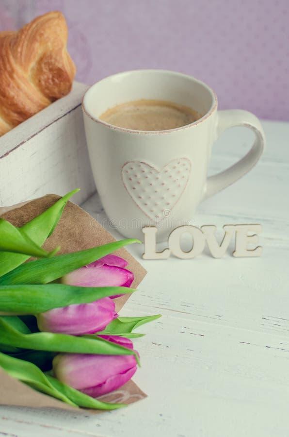 La taza de café con los cruasanes, el ramo de tulipanes rosados y la palabra de madera AMAN imagenes de archivo