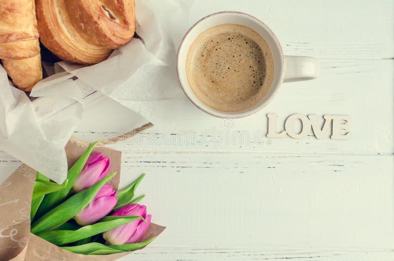 La taza de café con los cruasanes, el ramo de tulipanes rosados y la palabra de madera AMAN foto de archivo