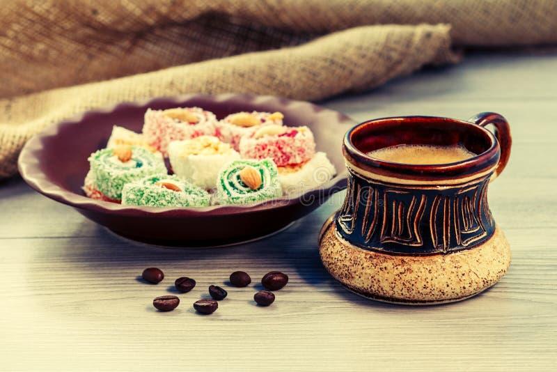 La taza de café con los granos de café y el placer turco en la arcilla plat fotos de archivo