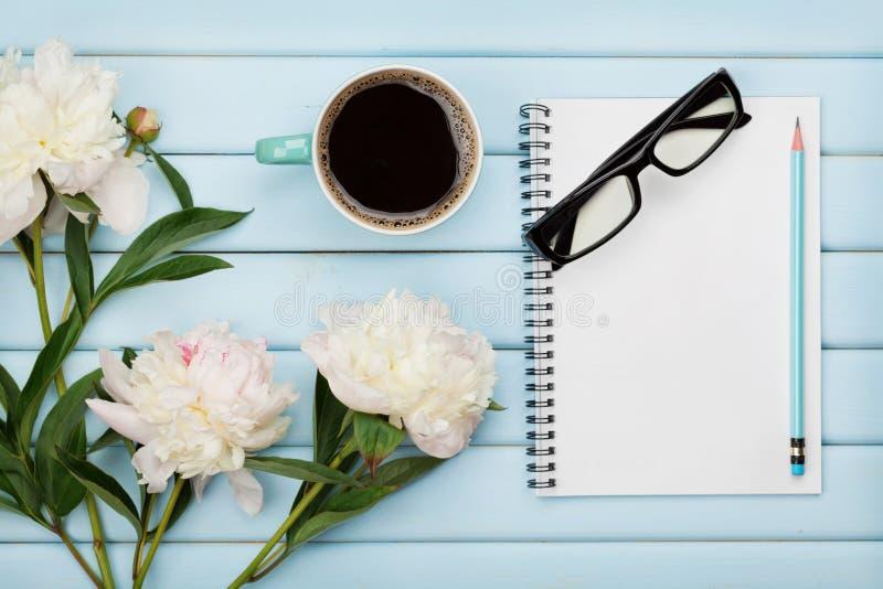 La taza de café de la mañana, el cuaderno vacío, el lápiz, los vidrios y la peonía blanca florece en la tabla de madera azul, des imágenes de archivo libres de regalías