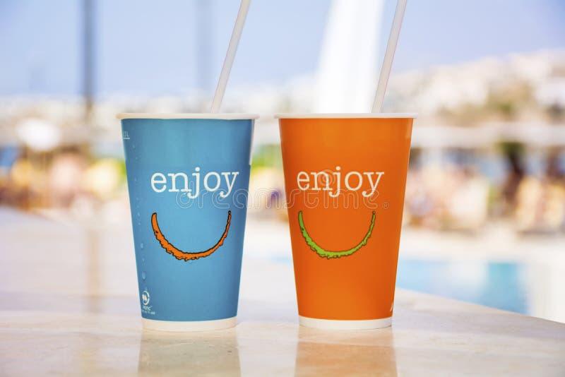 La taza de café de papel azul y anaranjada con la paja y disfruta de la muestra fotografía de archivo