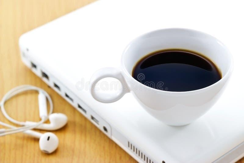 La taza de café en el ordenador portátil y el auricular blancos, relaja tiempo y negocio imagen de archivo