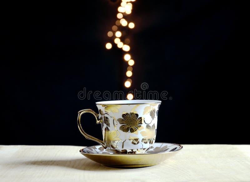 La taza de café en llamarada enciende el fondo imagen de archivo