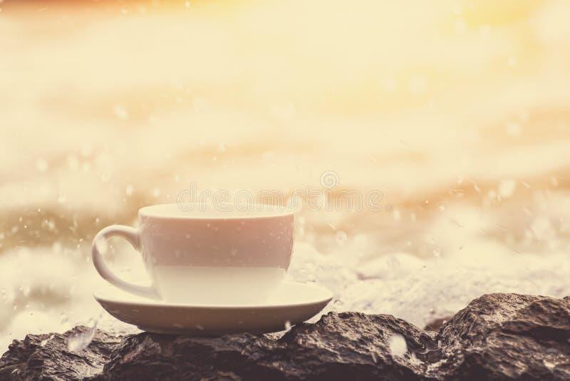 La taza de café en la piedra en la playa y el agua salpican fotografía de archivo