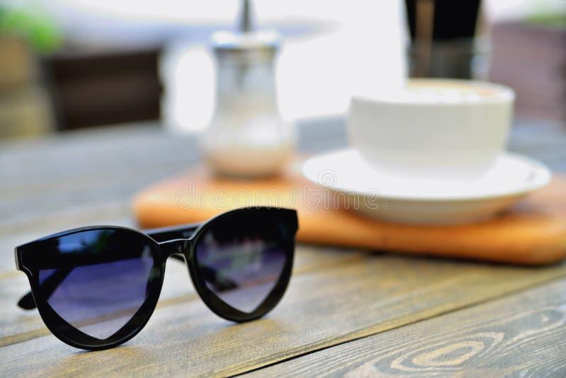 La taza de café en un soporte de madera está en la tabla por una mañana del verano del café, gafas de sol en el primero plano foto de archivo libre de regalías